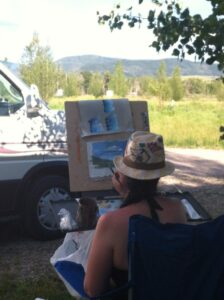 Painting outside with a hat on